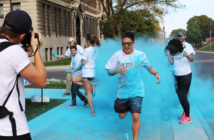 A student club member running in a race while being splashed with colored chalk powder