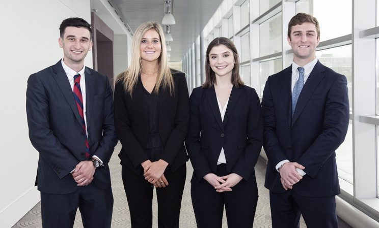Four students smiling after presenting their senior capstone project