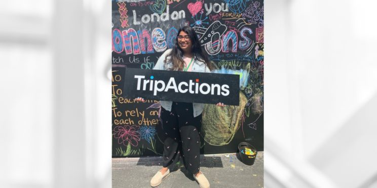 Student holds banner at her summer internship with TripActions
