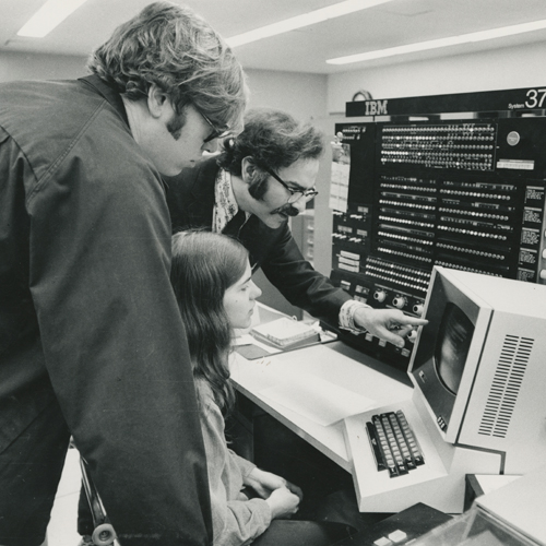 professor teaching a student on a computer in 1973