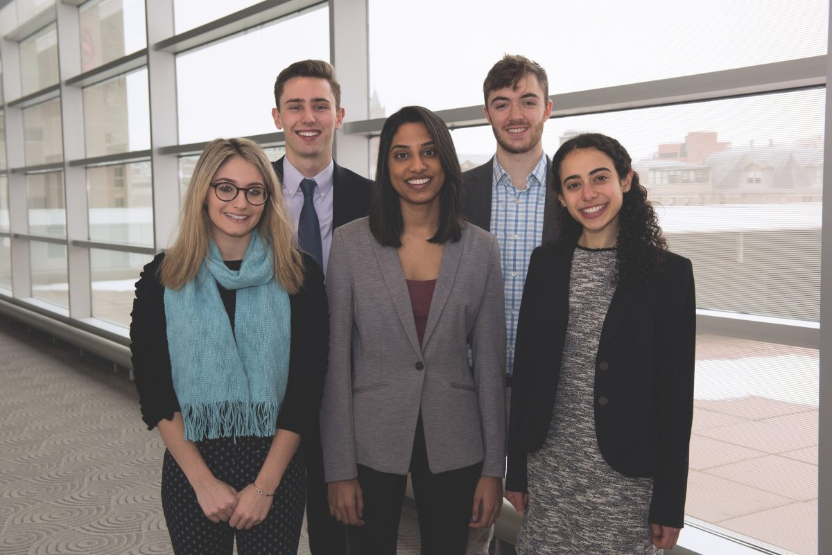 The five students who were selected for D'Aniello internships pose in front of the Milton Room.