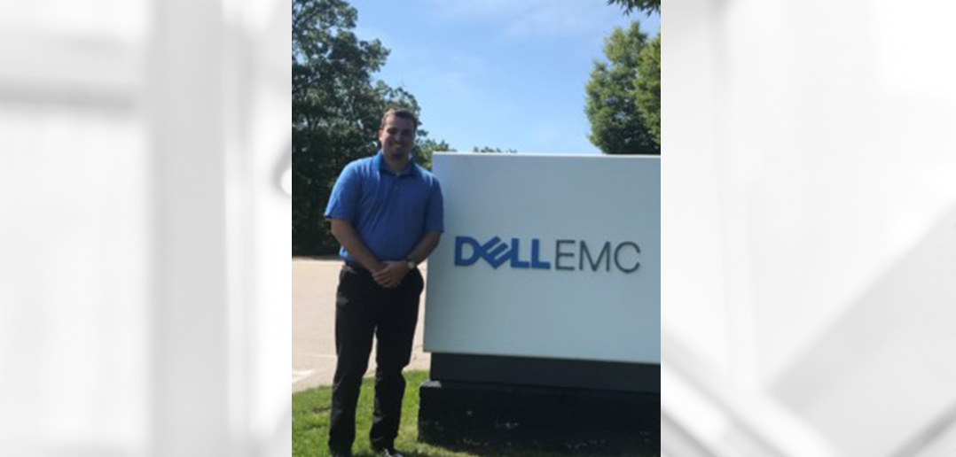 Student John Fenton standing in front of Dell sign during his internship experience