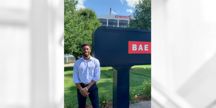 Male student standing outside of BAE Systems building by company sign during his internship