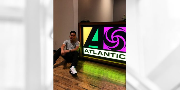 student sitting by Atlantic Records sign during internship