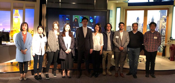 a group of master students posing for a photo at a TV set in NYC