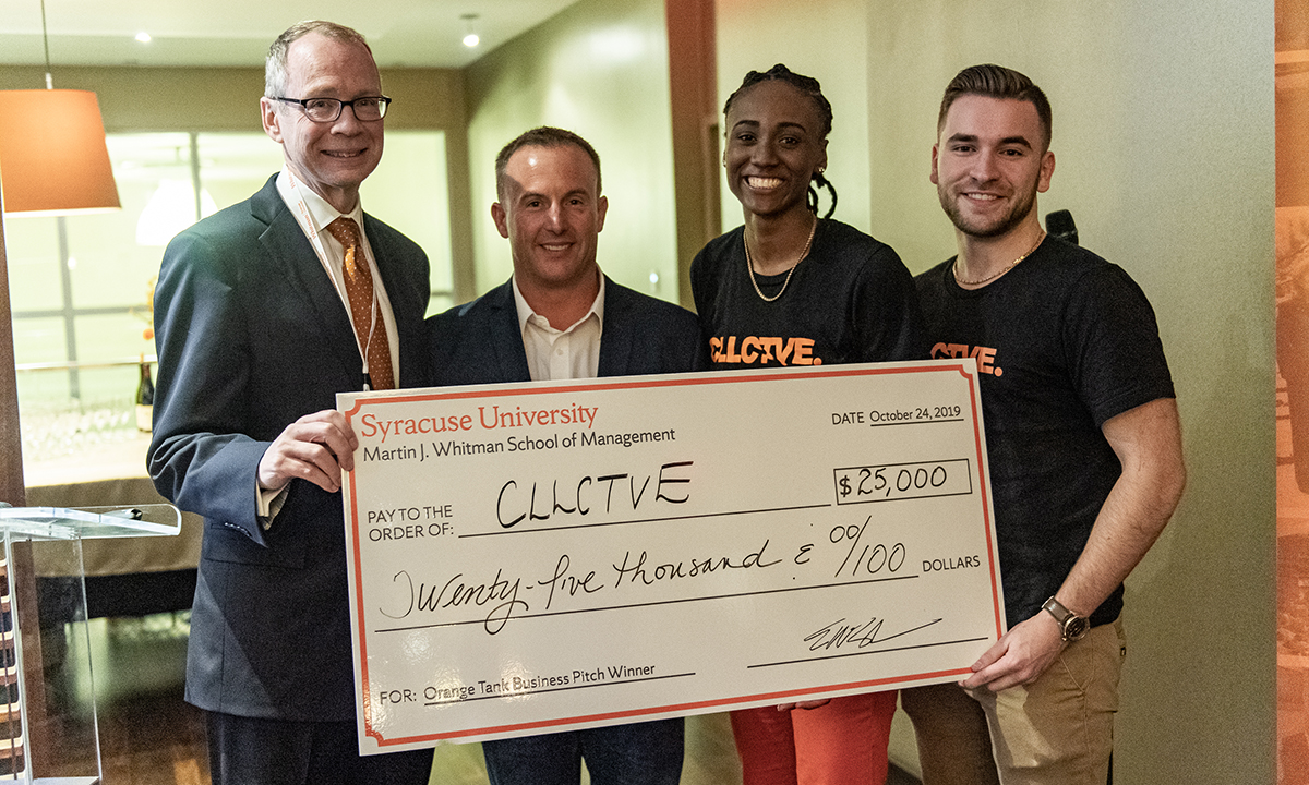 Gene Anderson and John Torrens, standing with first place winners and a large check at the 2019 Orange Tank business pitch competition