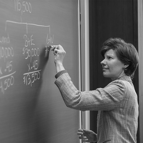 Professor writing on black board