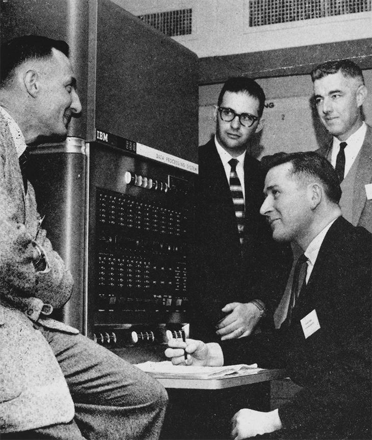 Men stand around first computer