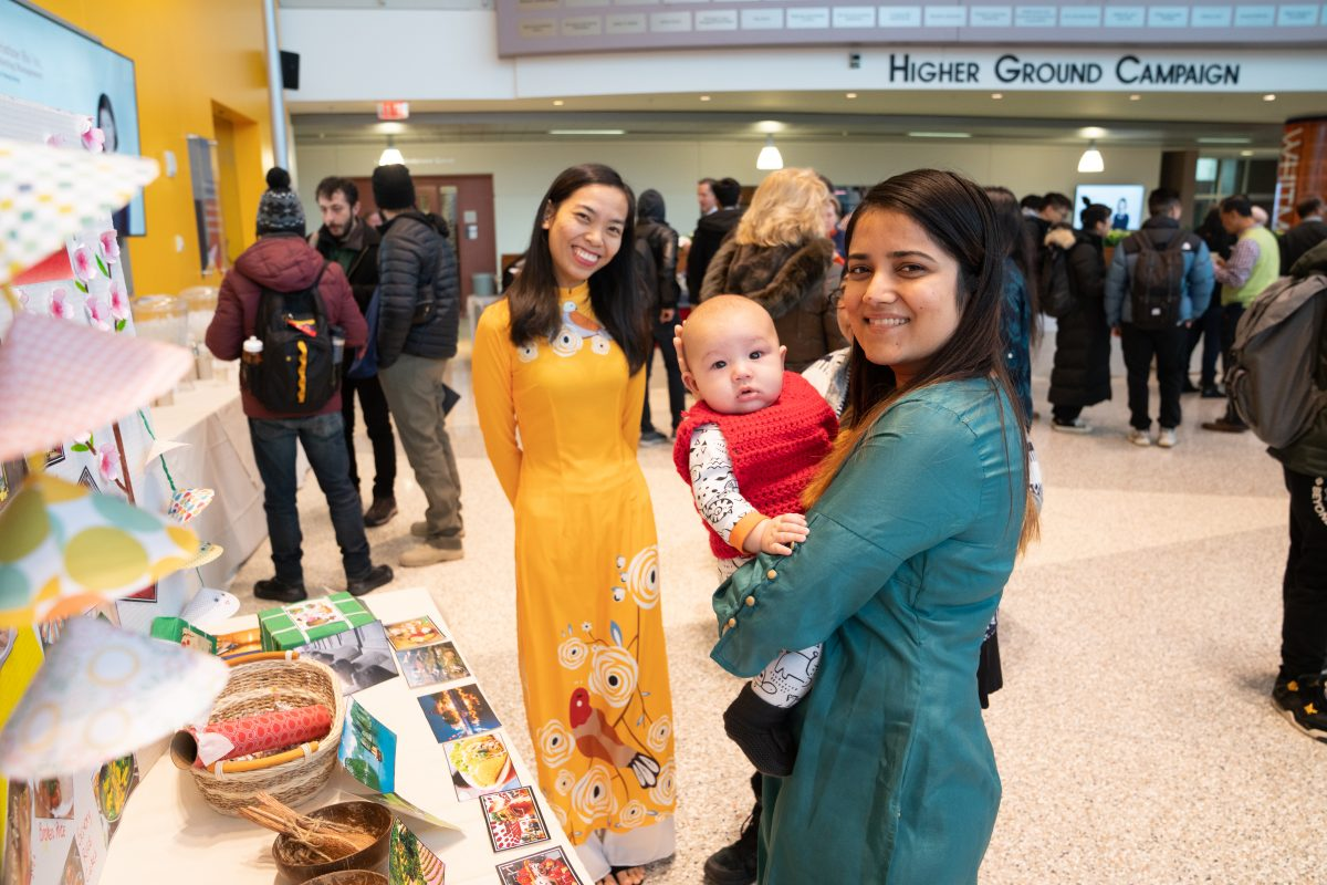 students posing with baby in front of international informational table