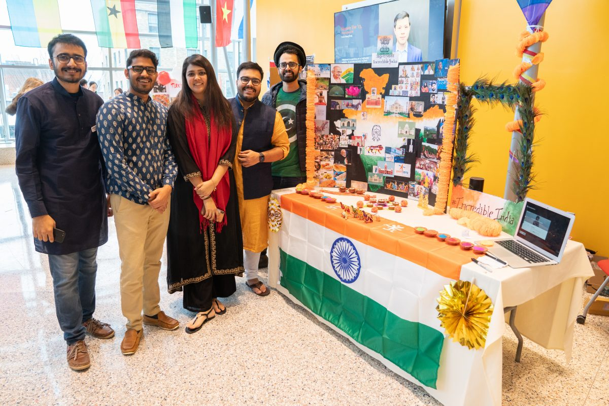 students posing in front of international informational table