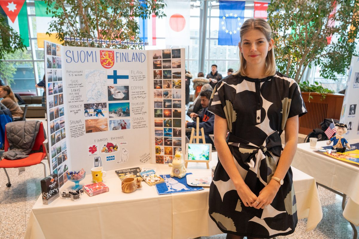 student posing in front of informational table