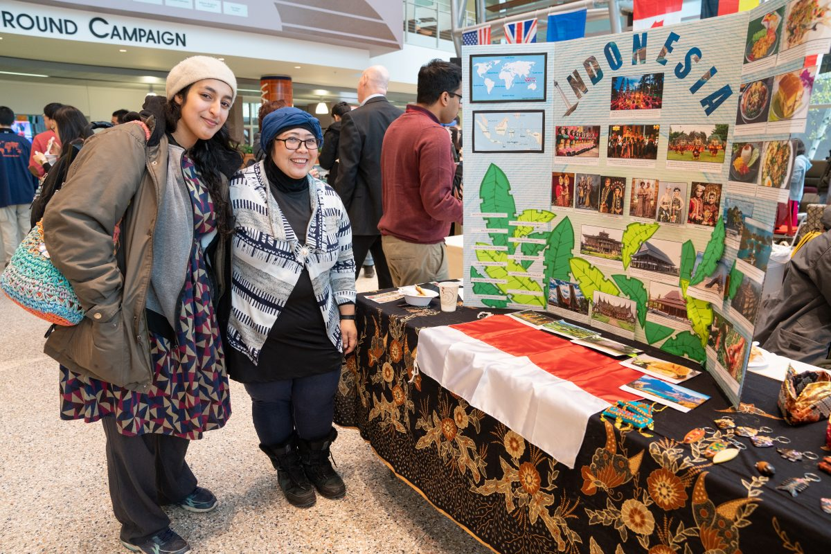 students posing in front of informational table