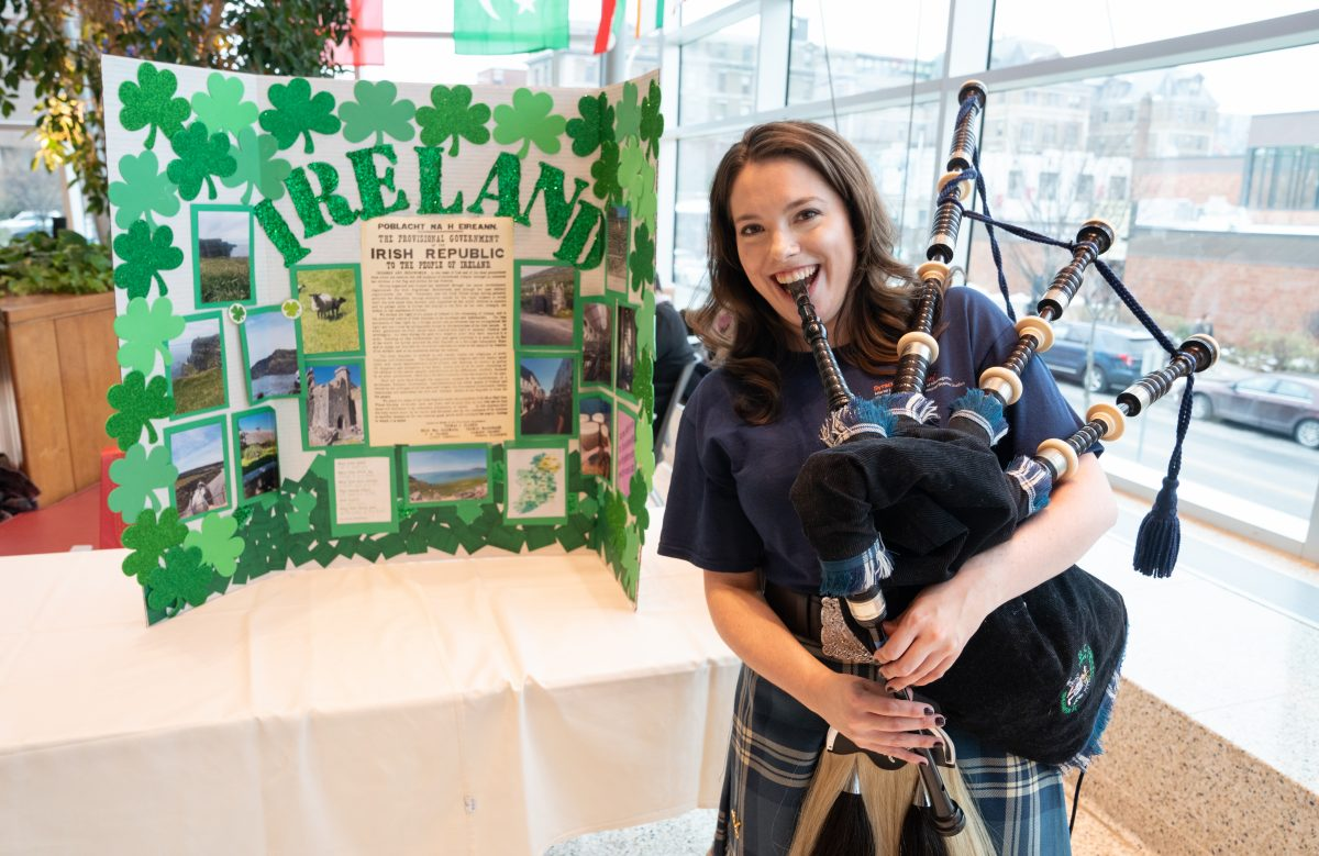 student posing in front of Ireland table with bagpipes