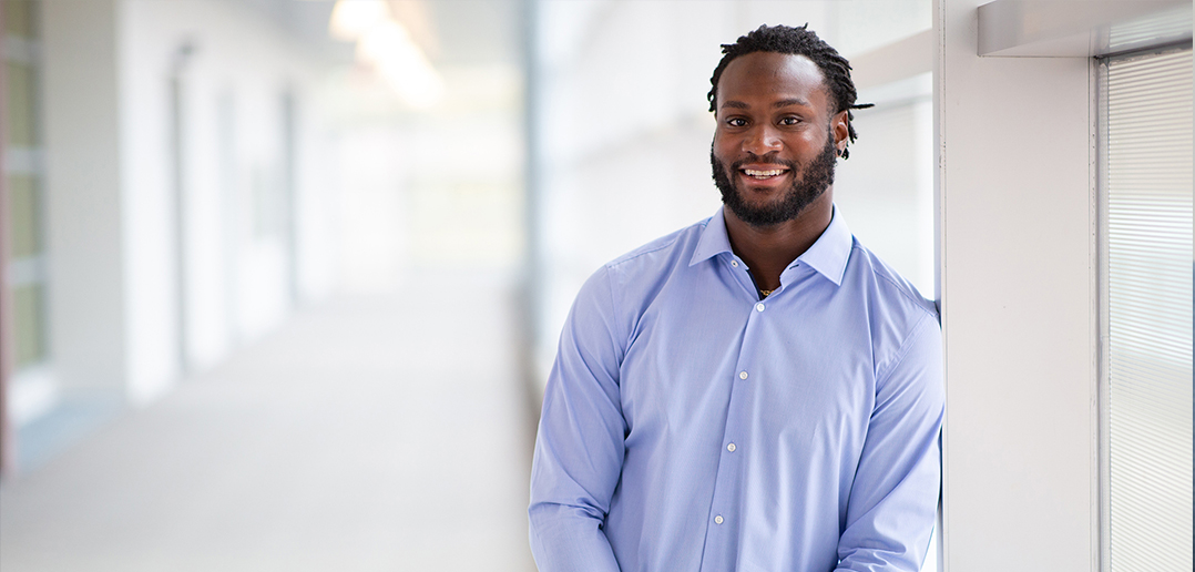 Latavius Murray dressed up in a button up shirt, standing in a hallway at the Whitman School