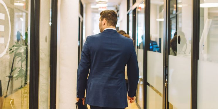 a student walking through a corporate hallway in a suit