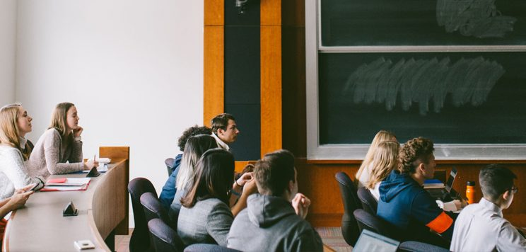 students looking at a professor giving a lecture in a classroom