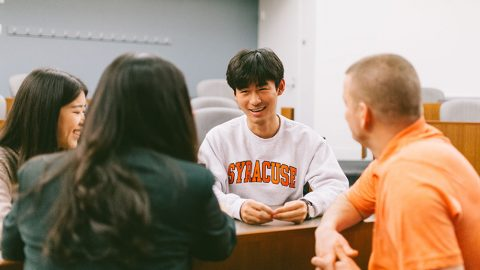 four master's students talking in a small group in a classroom environment