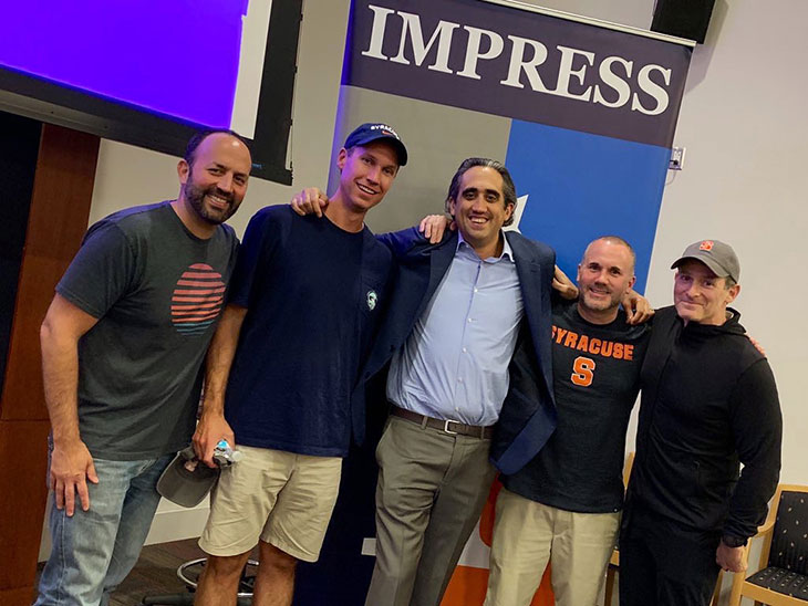 Seth Weigner and four friends pose infront of the IMPRESS banner