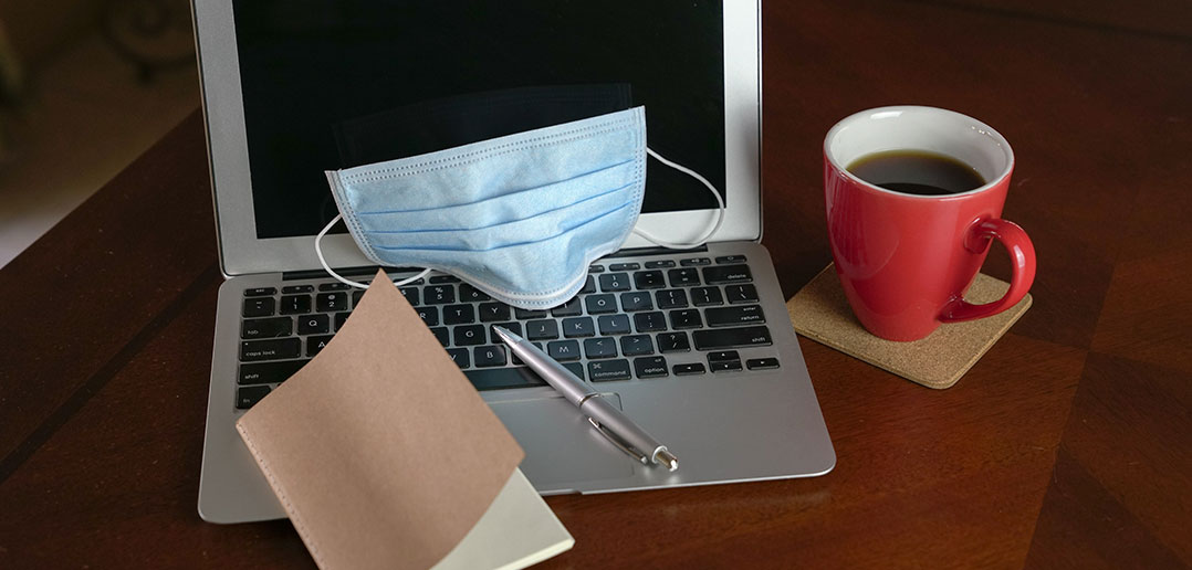 laptop, cup of coffee, notebook, pen and face mask on a table