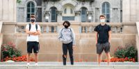 three students standing on the steps outside of the Hall of Languages wearing masks at Syracuse University