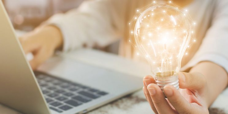 a person's hand holding a lightbulb and typing on a laptop