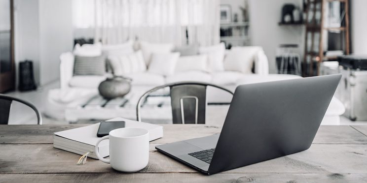 a living room with a desk set up, a laptop, coffee mug, notebook and phone set on to
