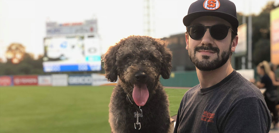Brian Albanese poses at a Syracuse Mets game with his dog