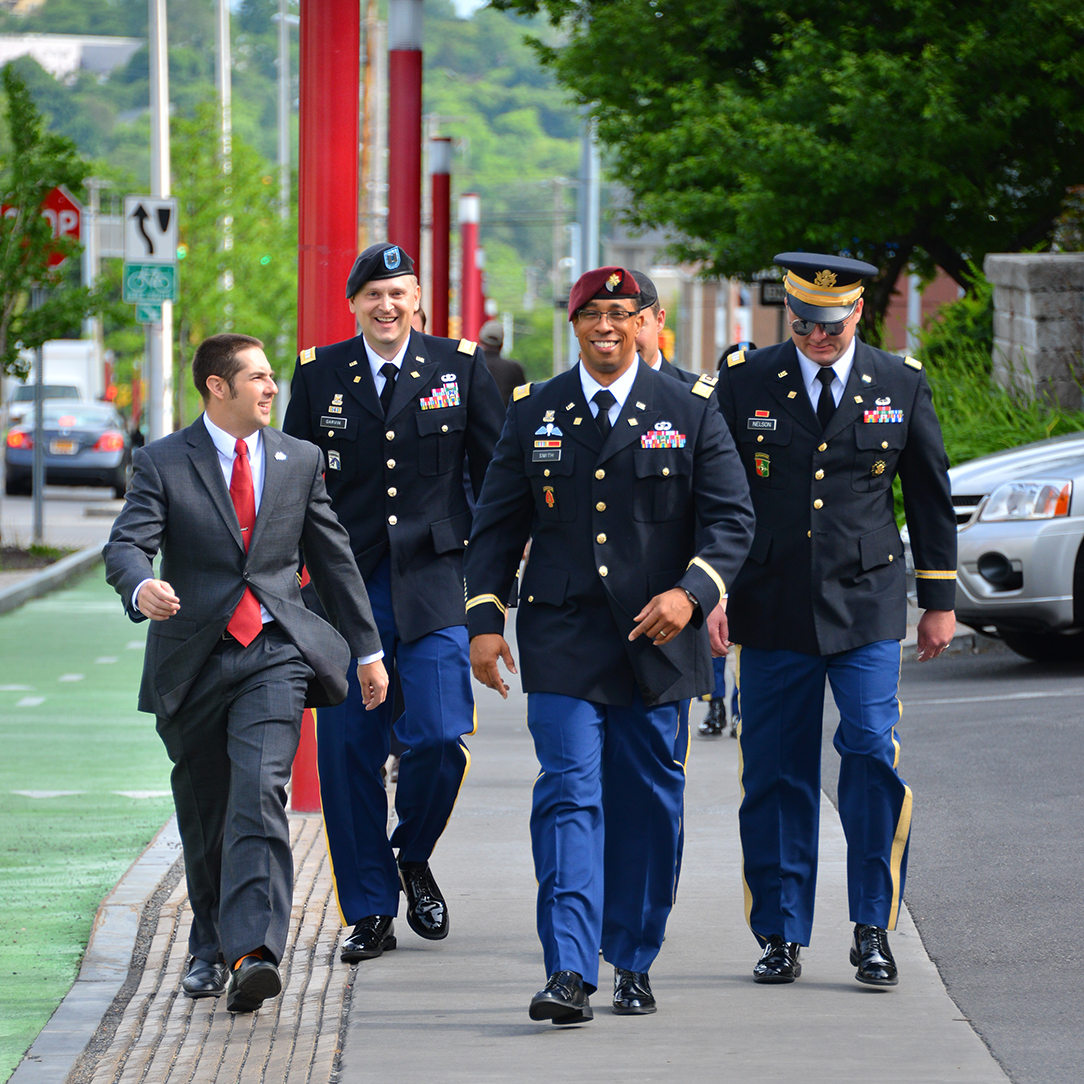 a group of DCP students in dress blues walking on the sidewalk