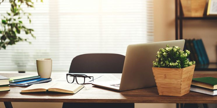 a desk in front of a window in a home with a laptop, plant, books, glasses, paper and coffee mug