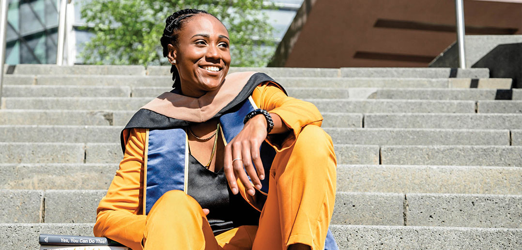 Kelsey Davis sitting on the Newhouse steps with an orange suite and her graduation outfit