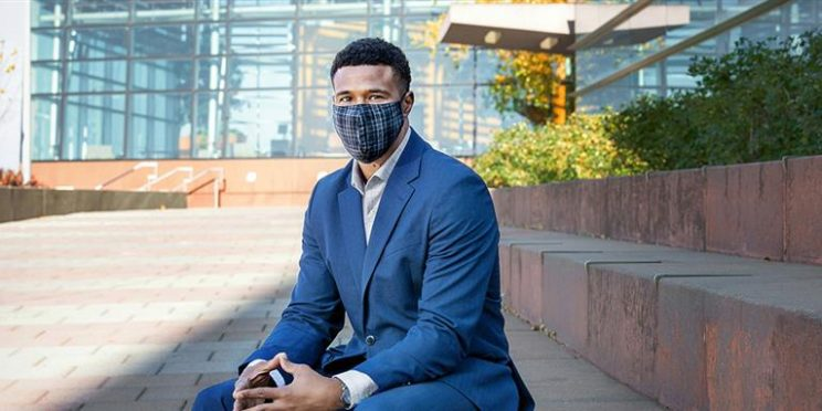 photo of El-Java outside the Whitman School, posing with a suit and mask