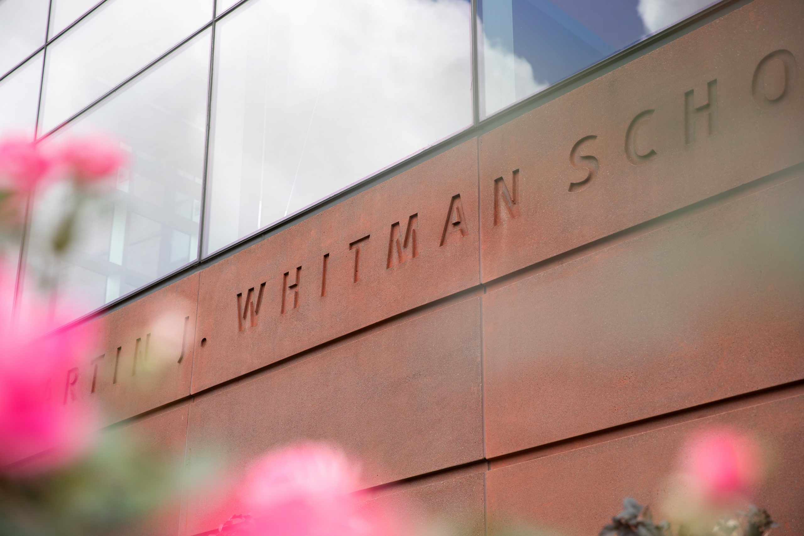 The building name carved into the front of Whitman School of Management is surrounded by landscaping.