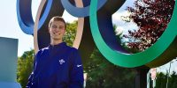 photo of Ryan Baker standing in front of the Olympic rings